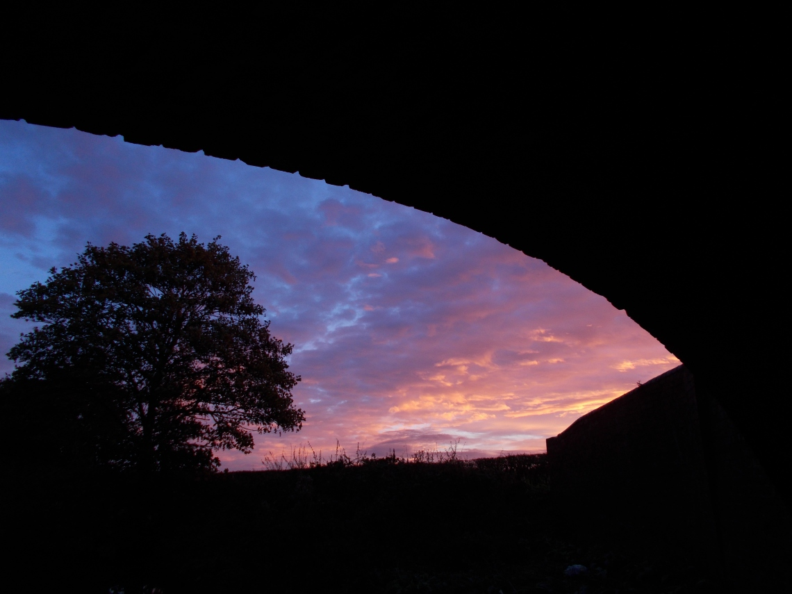 From under a canal bridge, dawn breaks